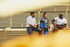 Blue-collor workers during lunch break. Laughing. Female Asian, male African-American and male Caucasian. Checkered shirt and white T-shirt. Primary color white. Secondary color yellow.